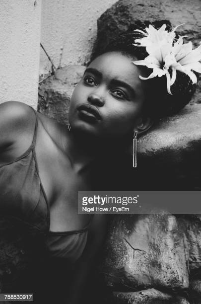 Thoughtful Woman Wearing Flowers Leaning On Rock By Wall