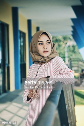 Thoughtful Woman Wearing Hijab While Standing By Railing