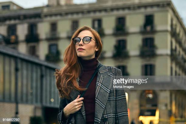 thoughtful woman wearing long coat walking in city - coat stock pictures, royalty-free photos & images