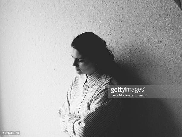 Thoughtful Woman With Arms Crossed Standing Against Wall