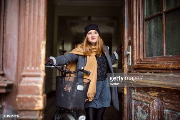 Nachdenkliche Frau mit Fahrrad auf Tür in Stadt