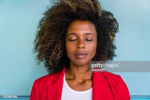thoughtful woman with closed eyes standing against wall - black blazer stock pictures, royalty-free photos & images