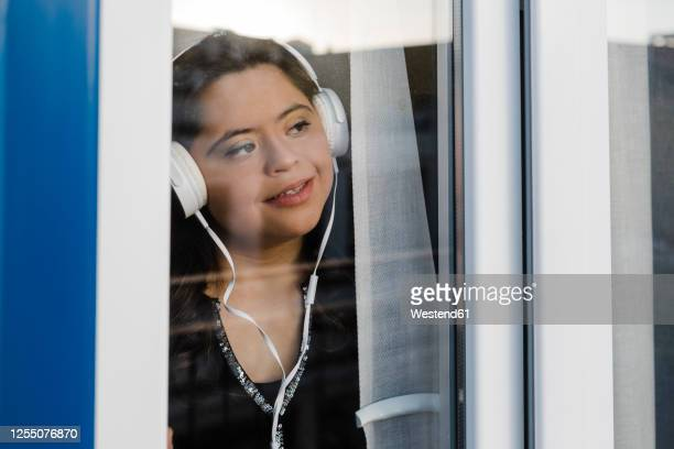 thoughtful woman with down syndrome listening music while looking through window at home - women wearing see through clothing stock pictures, royalty-free photos & images