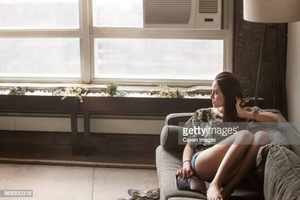 Thoughtful woman with tablet computer sitting on sofa