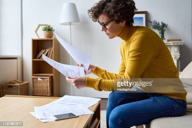 thoughtful woman working with tax documents - filing documents stock pictures, royalty-free photos & images