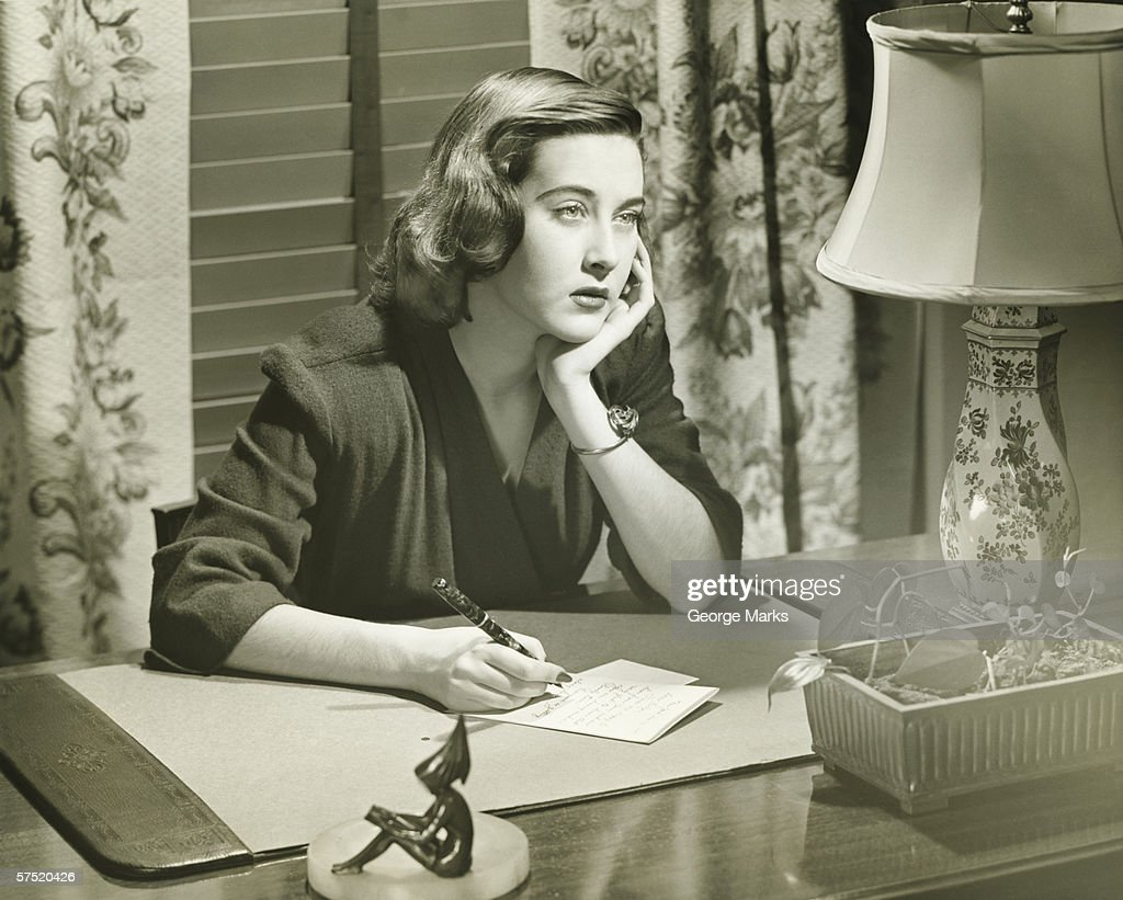 Thoughtful Woman Writing Letter At Desk Stock