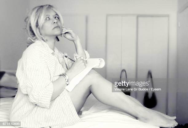Thoughtful Woman Writing On Paper While Sitting On Bed
