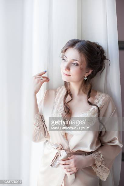 thoughtful women in nightie standing by curtain at home - women in slips stock pictures, royalty-free photos & images