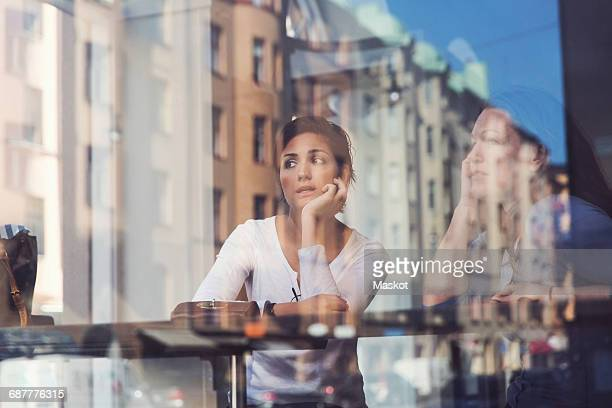 Thoughtful women seen through glass window at cafe