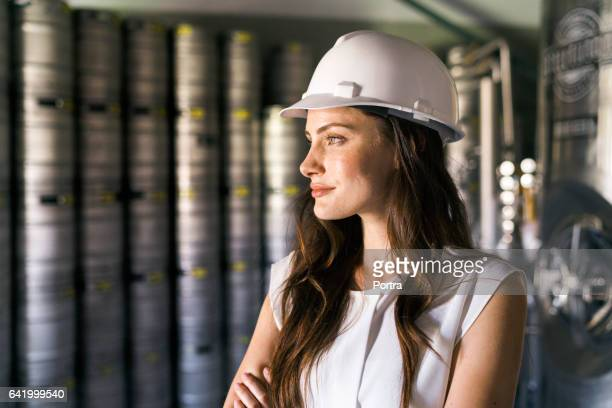 Thoughtful worker wearing hardhat in brewery