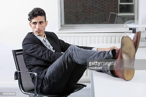 Thoughtful young businessman sitting with legs raised at desk in office