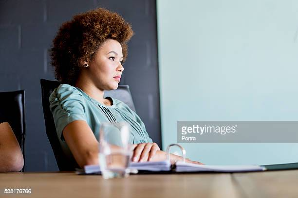 Thoughtful young businesswoman in board room