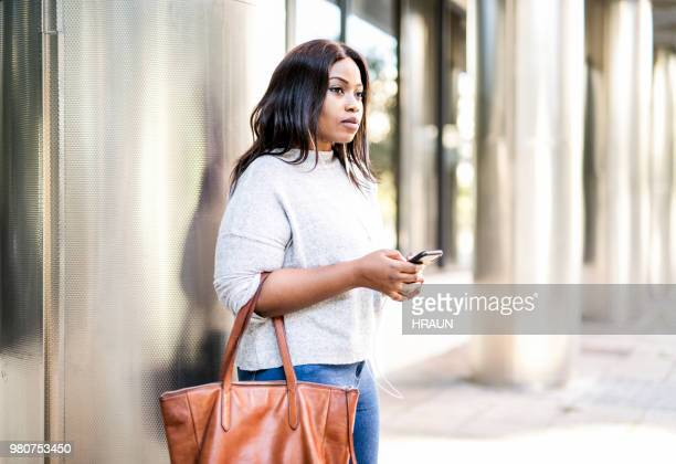 Thoughtful young businesswoman using mobile phone
