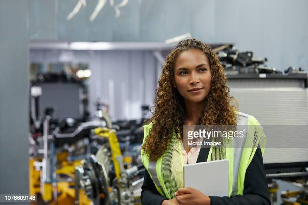 thoughtful young female engineer with document - mechanical engineering stock pictures, royalty-free photos & images