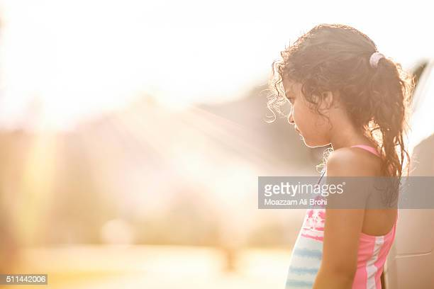 A thoughtful young girl standing in bright sunlight