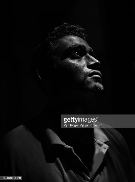 thoughtful young man looking away against black background - clair obscur photos et images de collection