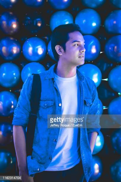 thoughtful young man looking away while standing against balls - jeffrey roque stock photos and pictures