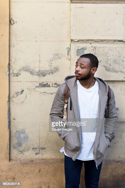 Thoughtful young man looking away while standing with hands in pockets against wall