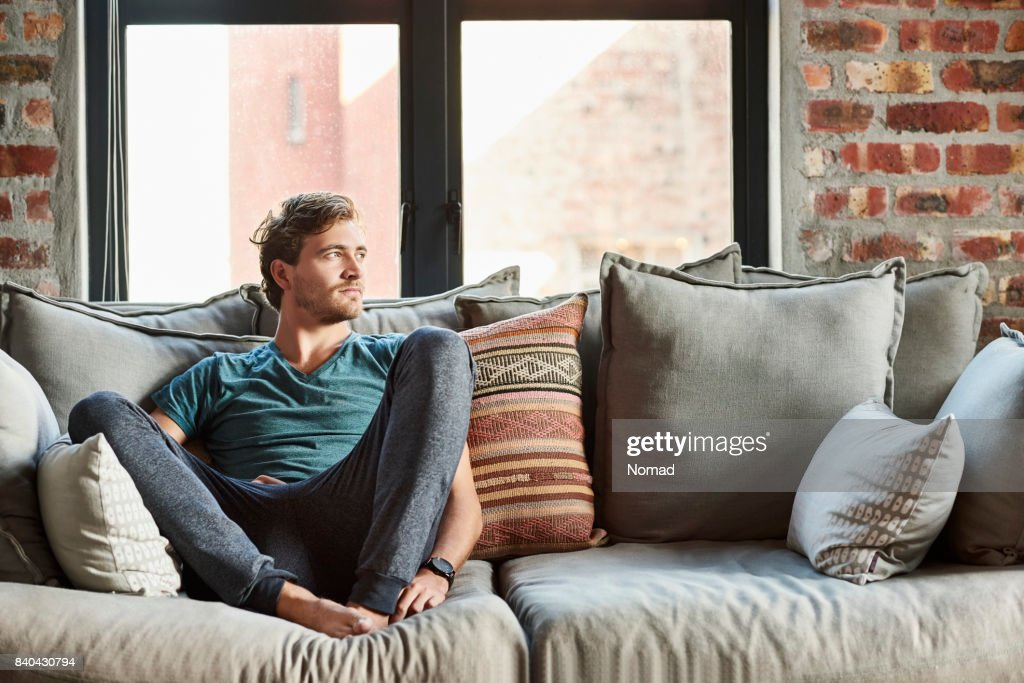 Thoughtful Young Man Relaxing On Sofa