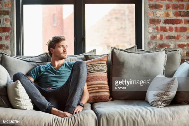 thoughtful young man relaxing on sofa at home - cushion stock photos and pictures
