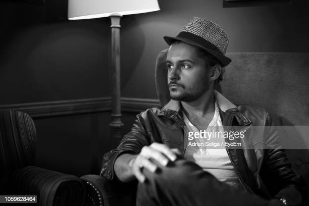 Thoughtful Young Man Sitting On Armchair At Home