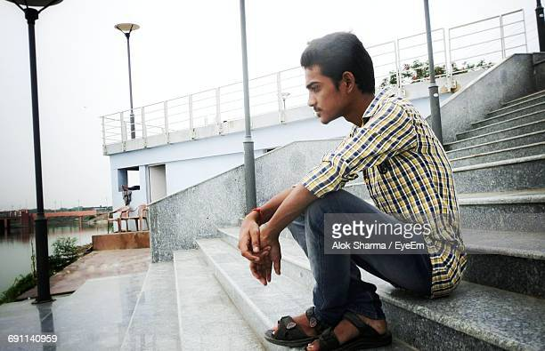Thoughtful Young Man Sitting On Steps By Lake Against Clear Sky