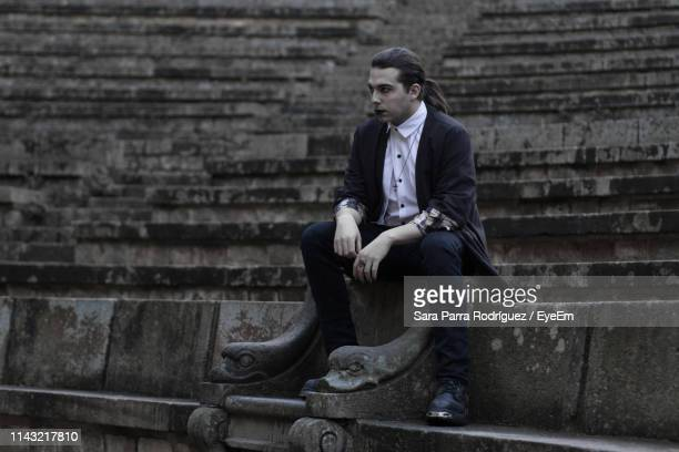 thoughtful young man sitting on steps - crossdresser photos et images de collection