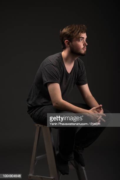 thoughtful young man sitting on stool against black background - stool stock pictures, royalty-free photos & images