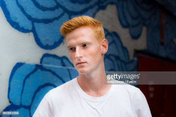 Thoughtful Young Man Standing Against Wall