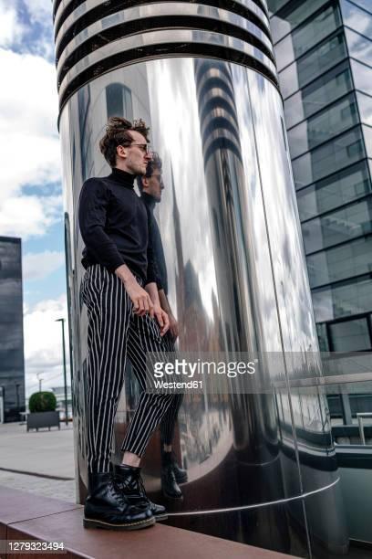 thoughtful young man standing by modern column in city - 25 29 jahre stock-fotos und bilder