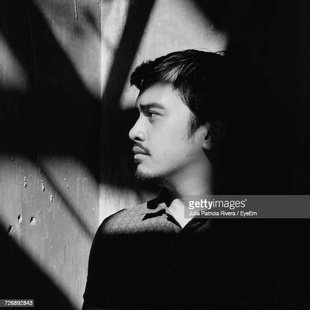 thoughtful young man standing by wall on sunny day - patricia rivera fotografías e imágenes de stock