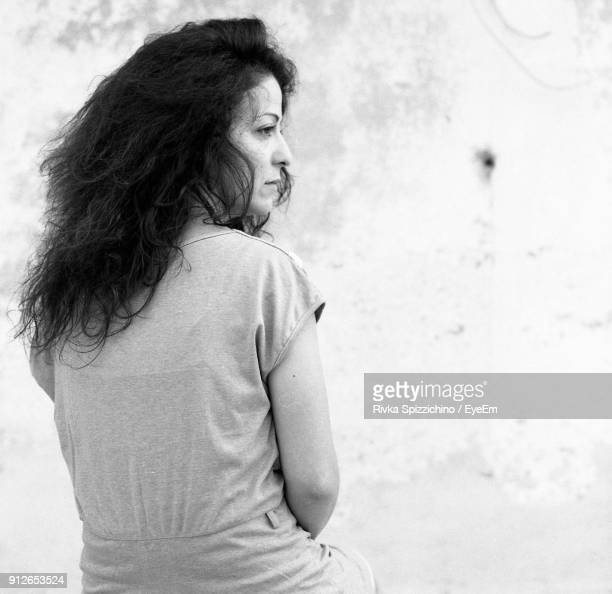 Thoughtful Young Woman Against Wall