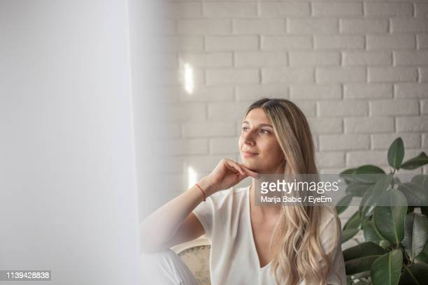 thoughtful young woman at home - marija mauer stock-fotos und bilder