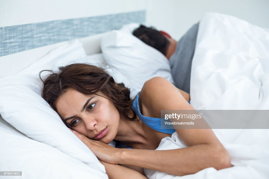 Thoughtful young woman besides husband in background lying on bed : Stock Photo