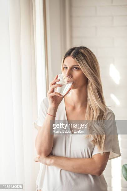 thoughtful young woman drinking water at home - marija mauer stock-fotos und bilder
