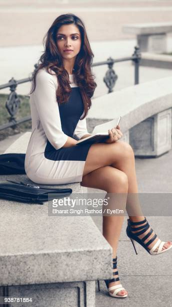thoughtful young woman holding book while sitting on seat in city - beautiful woman stock pictures, royalty-free photos & images