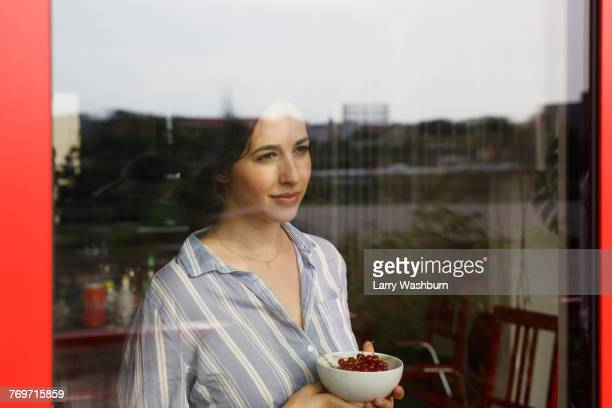 Thoughtful young woman holding bowl with red currants while looking through window