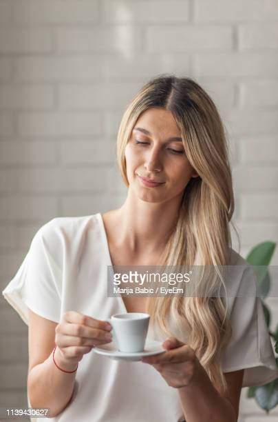 thoughtful young woman holding coffee at home - marija mauer stock-fotos und bilder