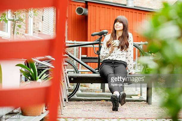 thoughtful young woman holding coffee cup while sitting on bench at cafe backyard - bench stock pictures, royalty-free photos & images