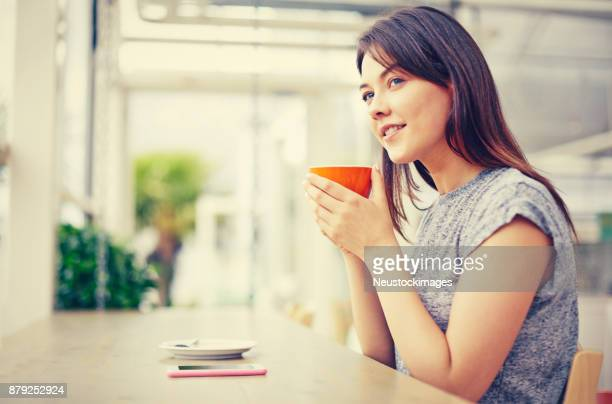 Thoughtful young woman holding coffee mug at restaurant