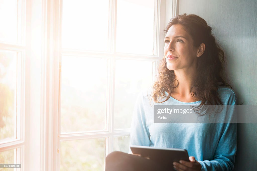 Thoughtful young woman holding digital tablet by window : Stock Photo