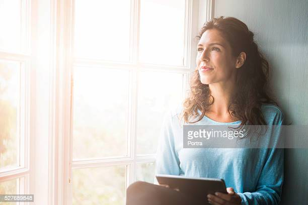 thoughtful young woman holding digital tablet by window - three quarter length stock pictures, royalty-free photos & images