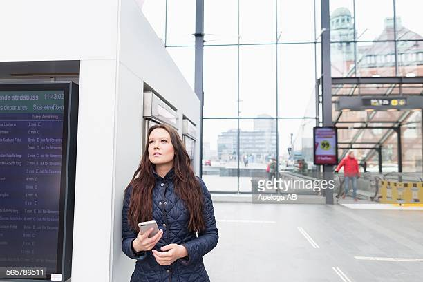 Thoughtful young woman holding mobile phone at railway station