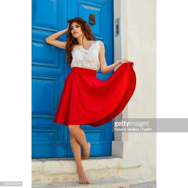 Thoughtful Young Woman Holding Red Skirt While Standing By Closed Door