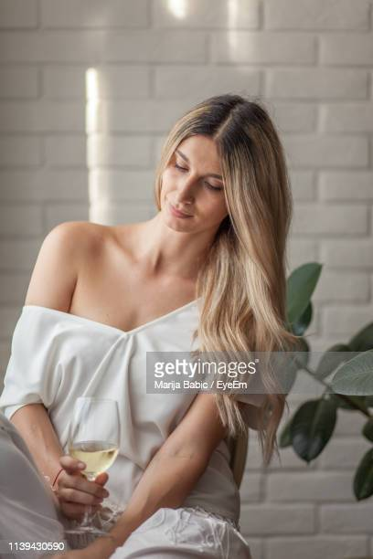 thoughtful young woman holding wine at home - marija mauer stock-fotos und bilder