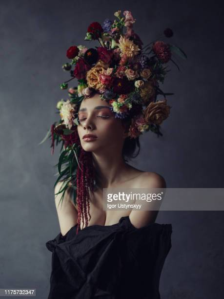 thoughtful young woman in floral headdress - body paint fotografías e imágenes de stock