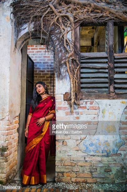 Thoughtful Young Woman In Sari Looking Away While Standing At Doorway
