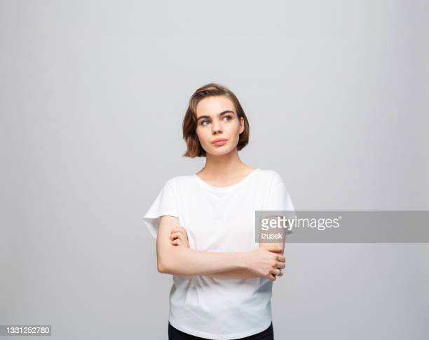 thoughtful young woman in white t-shirt - izusek stock pictures, royalty-free photos & images