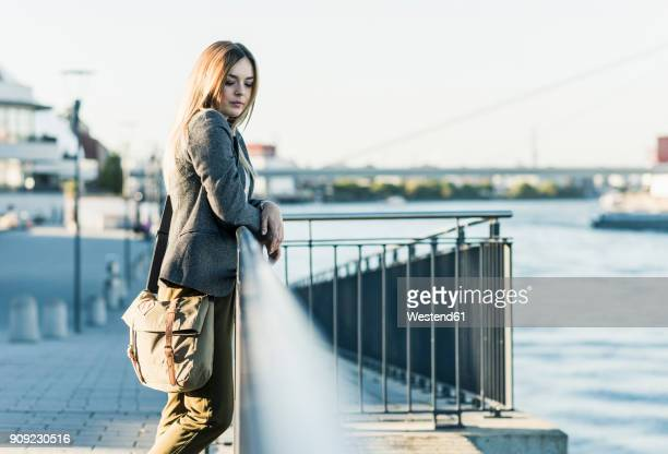Thoughtful young woman leaning on railing at the riverside