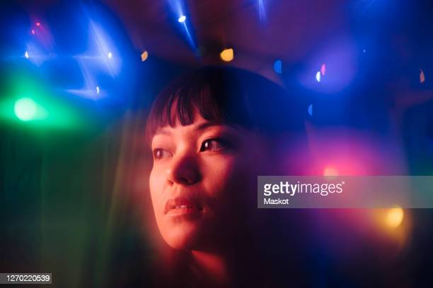 thoughtful young woman looking away amidst multi colored lights in restaurant - nightlife stock pictures, royalty-free photos & images